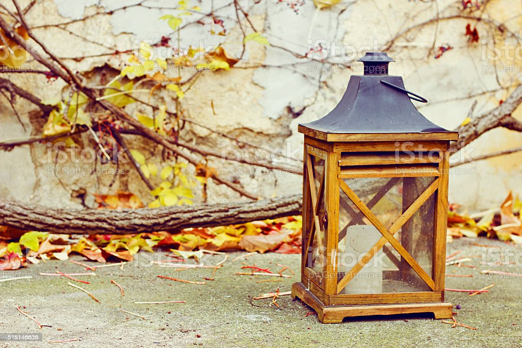 Old wooden lamp with a candle in autumn garden stock photo