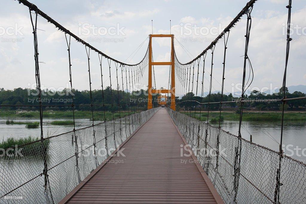 old wooden long pendant bridge cross the stream, on nature stock photo
