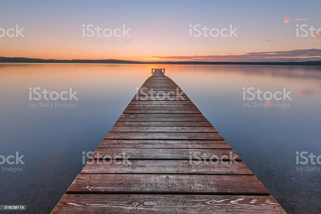 Old wooden pier on sunset stock photo