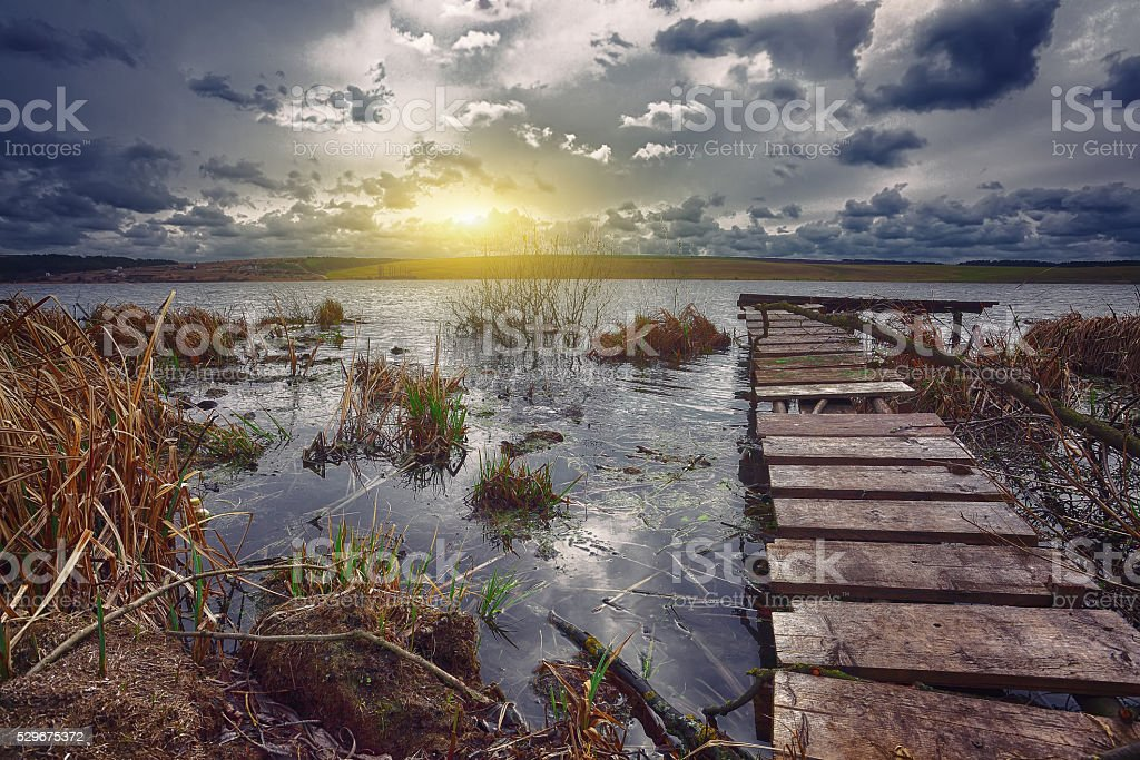 Old wooden pier with dry reed on sunset stock photo