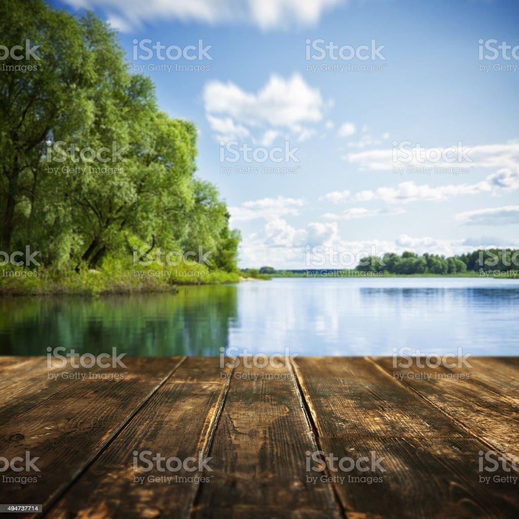 Old wooden planks and defocused summer landscape on background stock photo