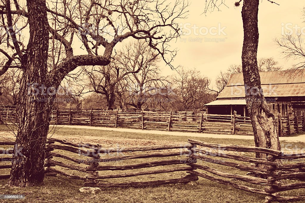 Old, wooden ranch fence and barn in sepia. stock photo