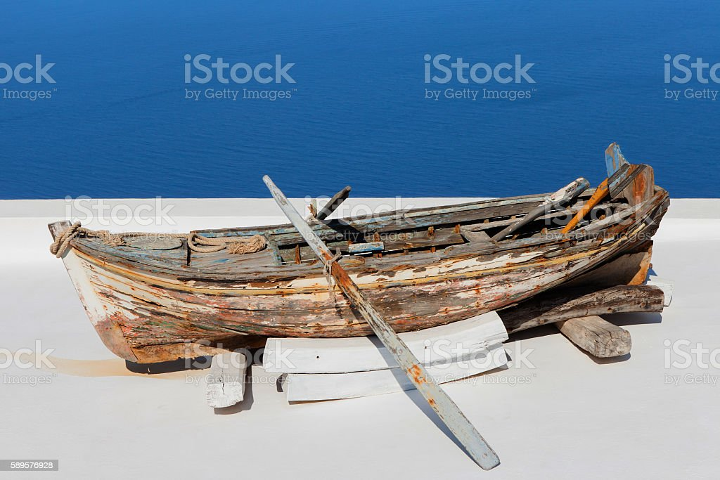 Old wooden rowing boat overlooking Santorini's bay stock photo