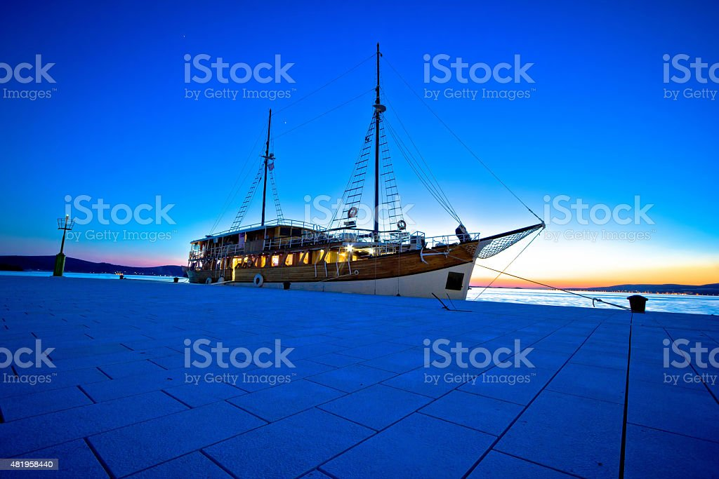 Old wooden sailboat at blue evening stock photo