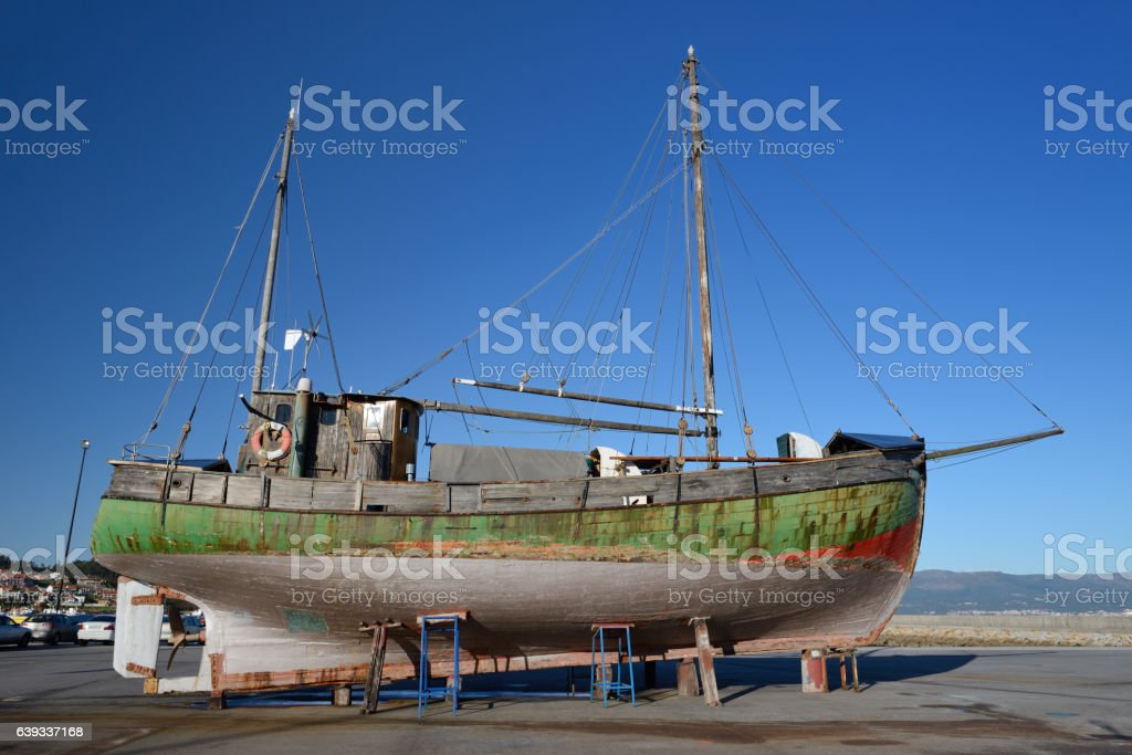 old wooden sailing vessel on supports stock photo
