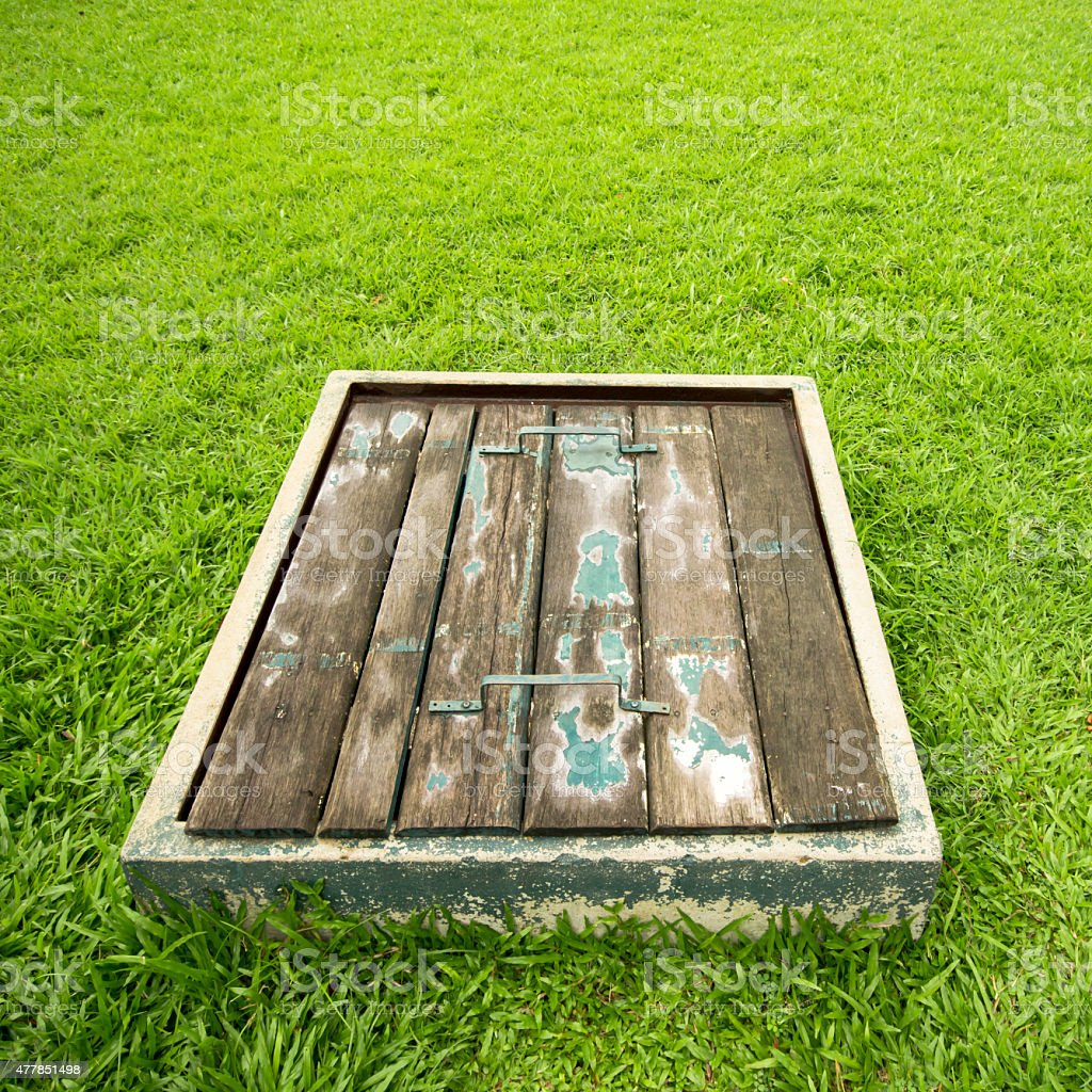 Old wooden sewer manhole on floor. green grass floor. royalty-free stock photo
