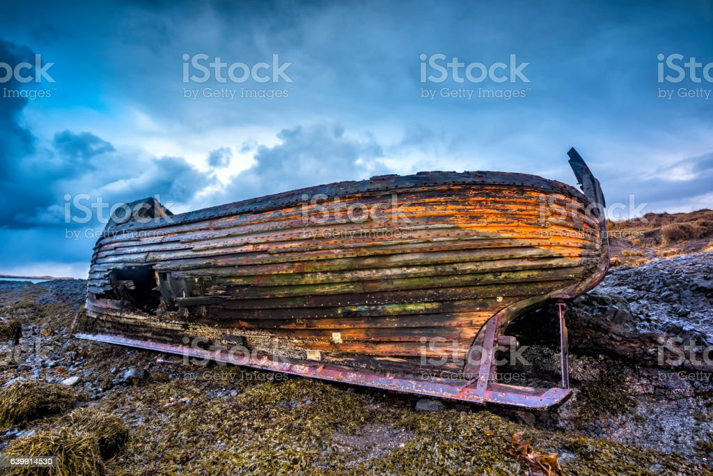 Old wooden ship on beach stock photo