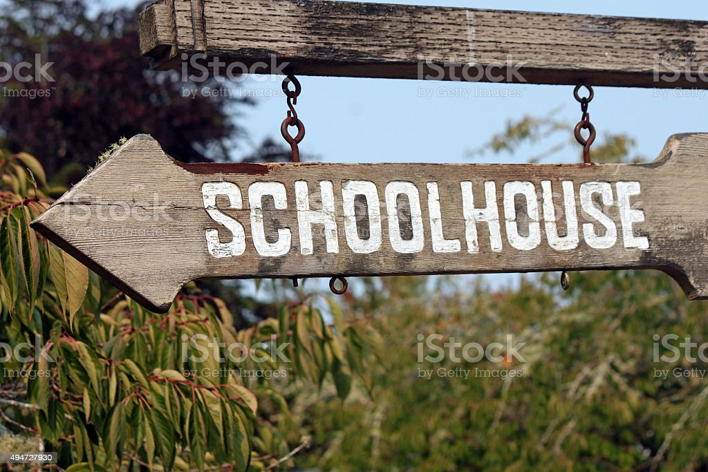 Old Wooden Sign Pointing to School stock photo