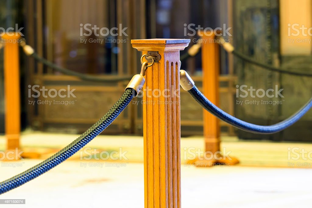 Old wooden stanchion post with blue rope, indoor stock photo