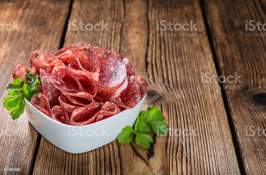 Old wooden table with sliced Salami stock photo