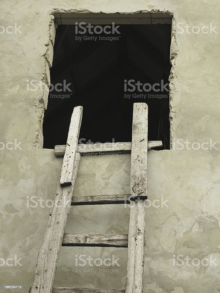 Old wooden vintage cuve ladder near a wall royalty-free stock photo