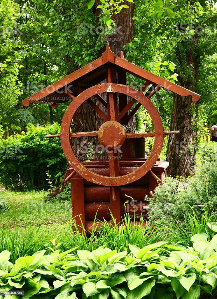 old wooden well with bin and steering weel stock photo