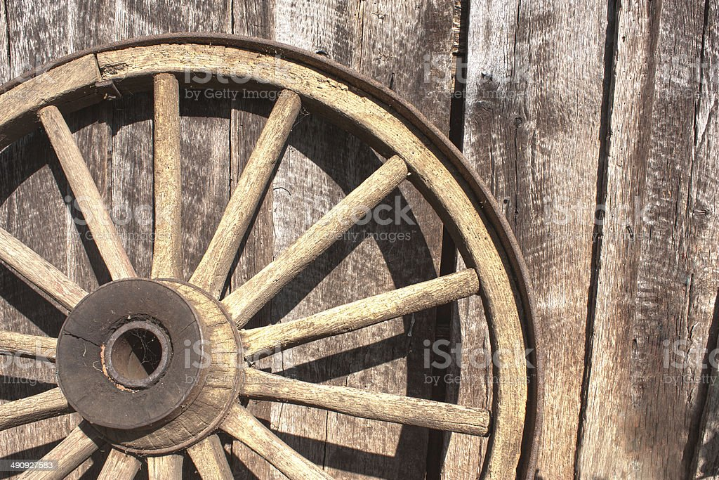 Old wooden wheel leaning against barn stock photo