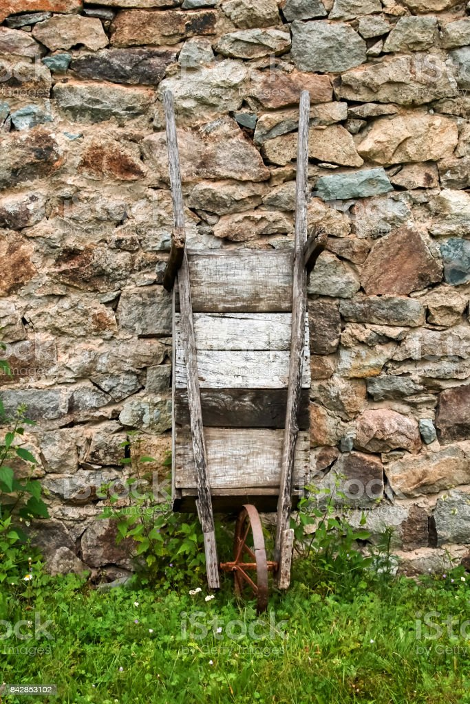 Old wooden wheelbarrow leaned against a stone wall stock photo