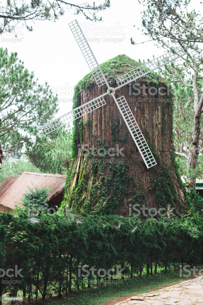 Old wooden windmill in park stock photo