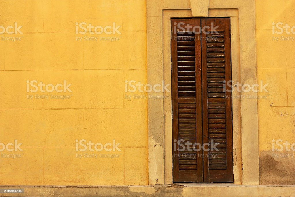 Old wooden window on yellow wall stock photo
