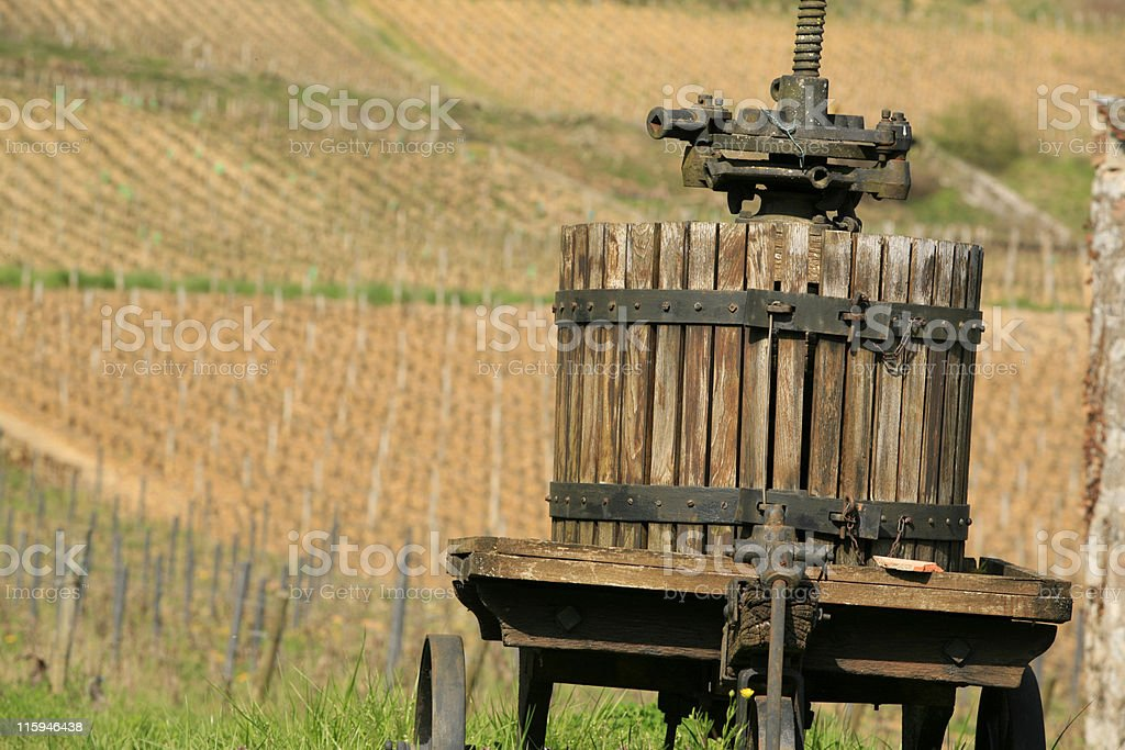 old wooden winepress in front of the vineyards stock photo