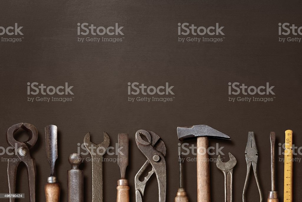 Old workshop hand tools aligned on a blackboard stock photo