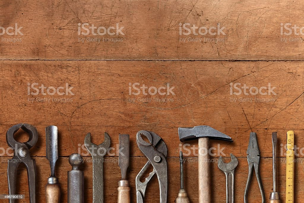 Old workshop hand tools aligned on a brown wooden table stock photo