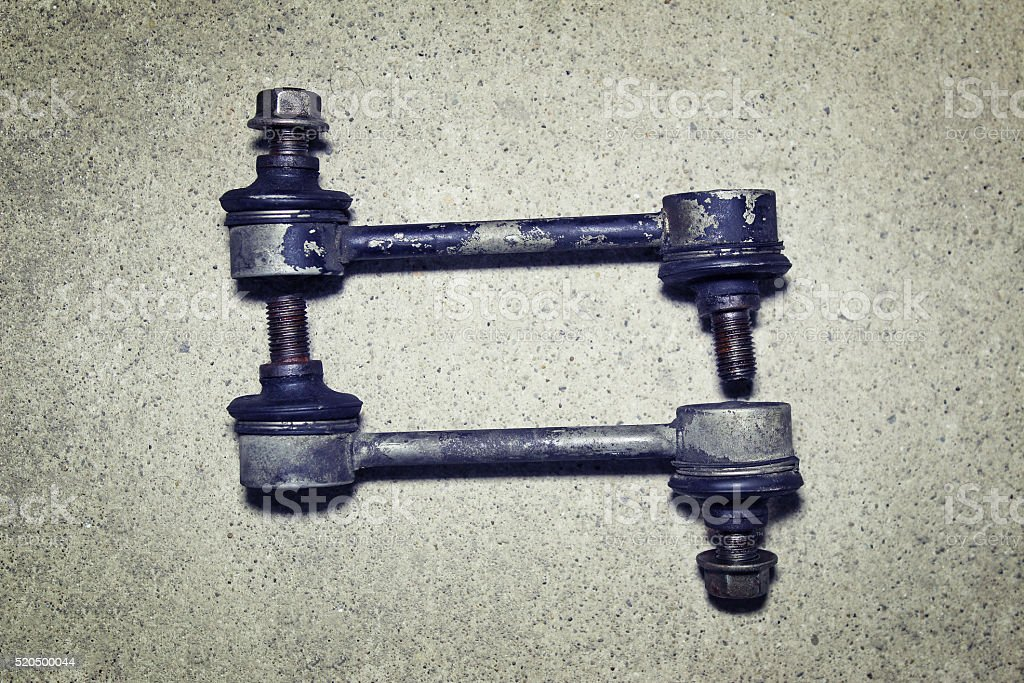 Old worn links stabilizer on a gray background stock photo
