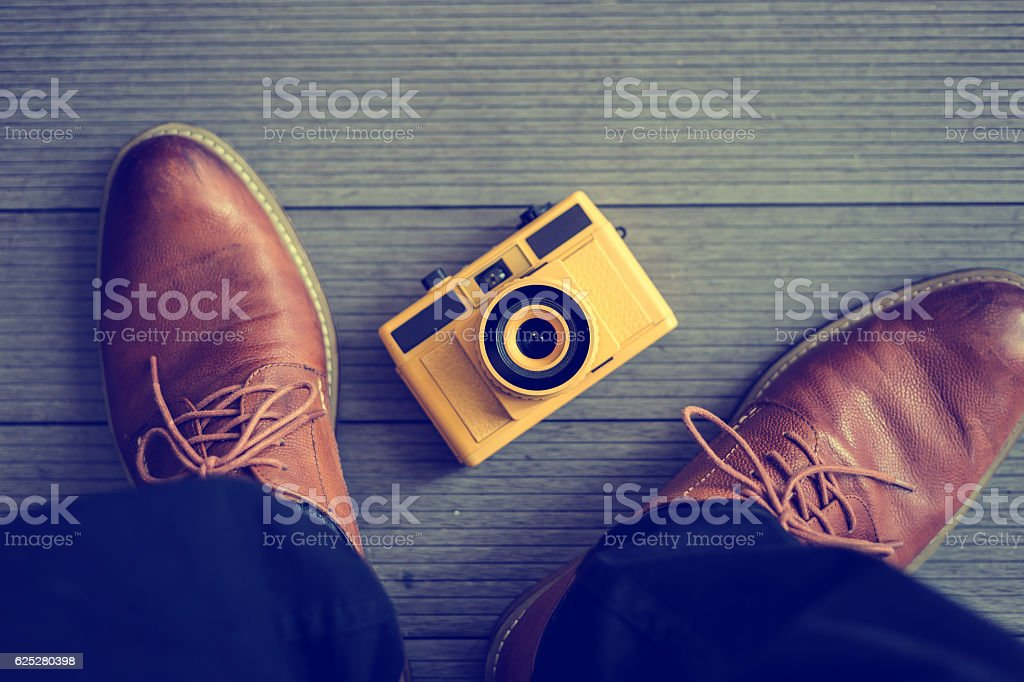 Old worn out brown leather shoes with camera stock photo
