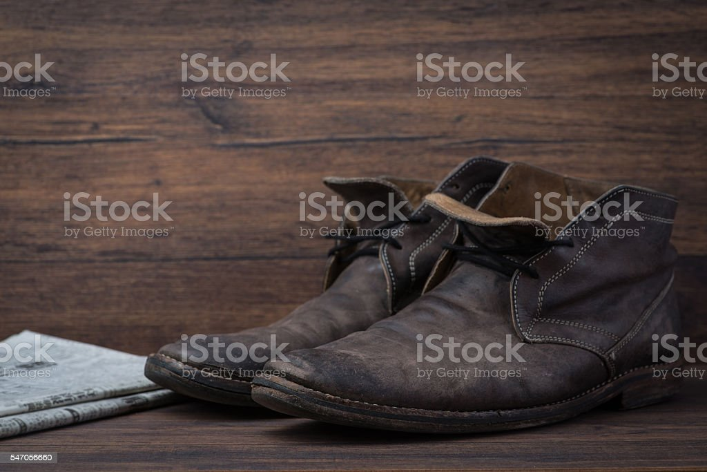 Old worn out brown leather shoes with newspaper stock photo