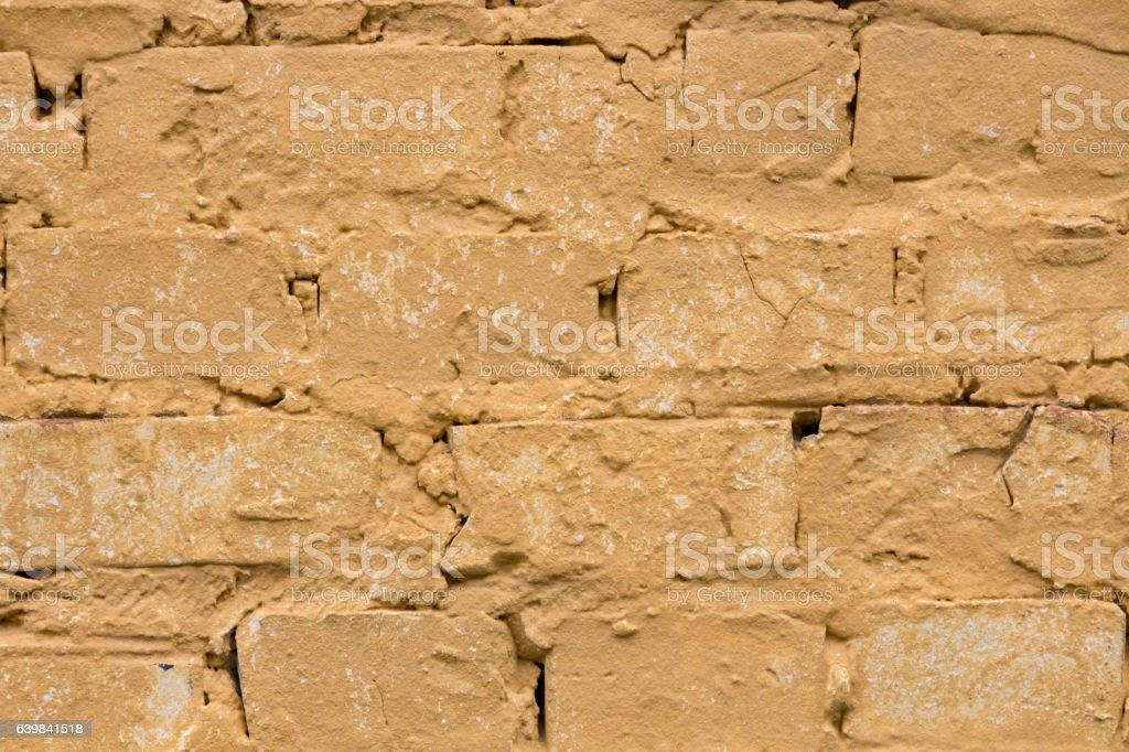 Old worn yellow brick wall background. stock photo