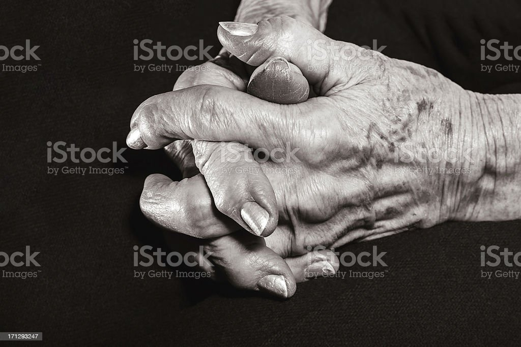 old wrinkled clasped hands distorted by arthritis stock photo