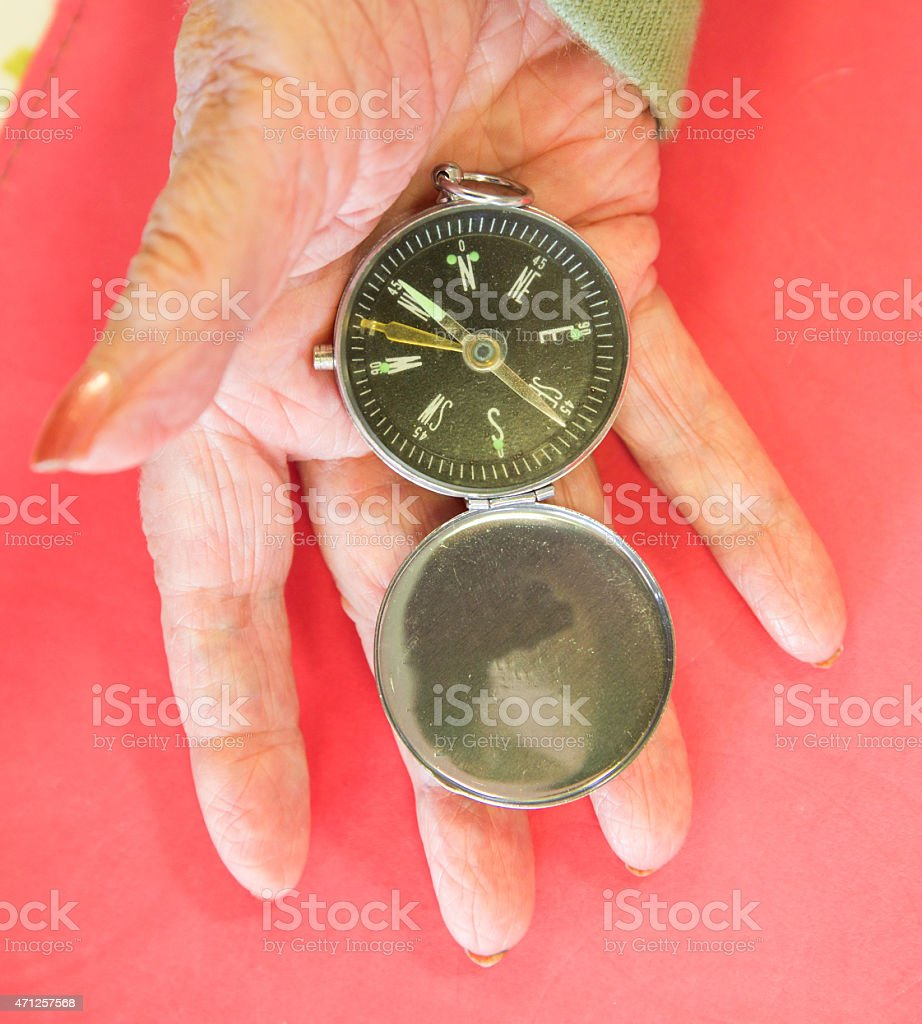 Old wrinkled hand holds a compass looking for direction stock photo