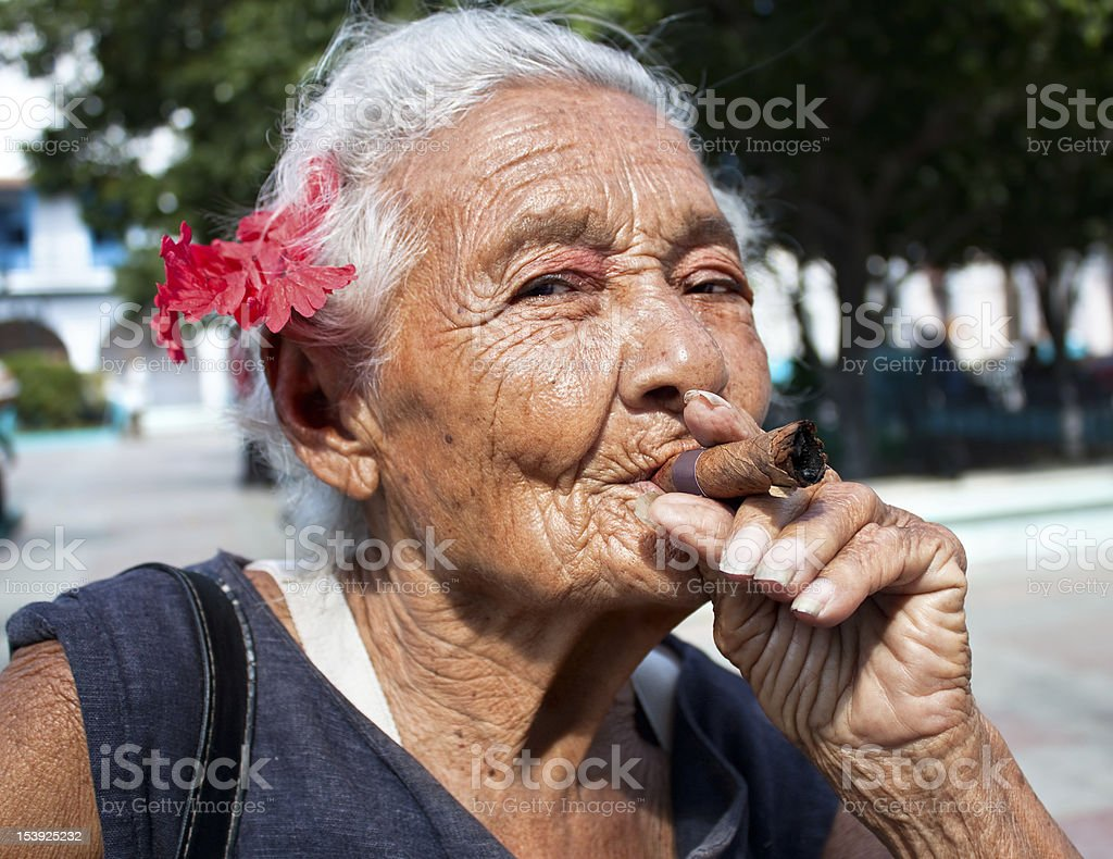 Old wrinkled woman with red flower smoking cigar stock photo