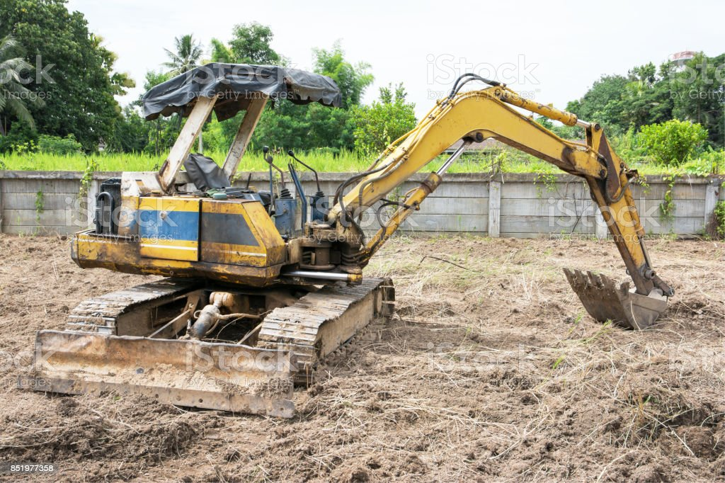 Old Yellow excavator parked.Old small excavator parked outdoor.Excavator parking off field stock photo
