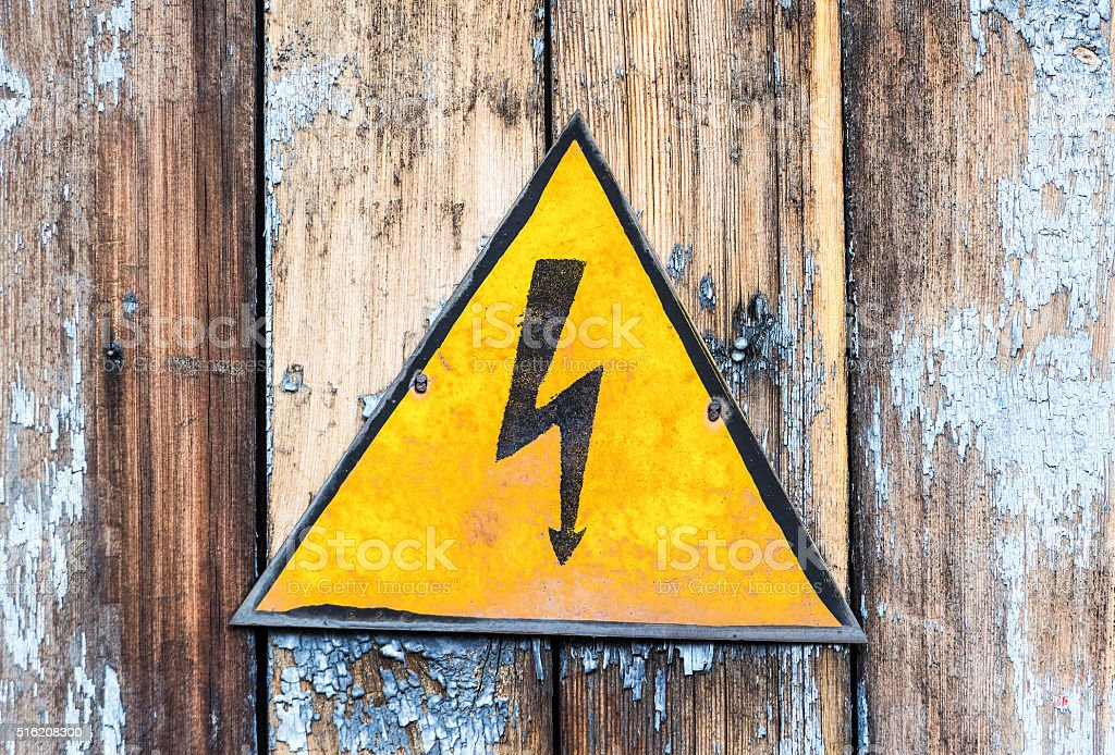 Old yellow high voltage caution sign stock photo