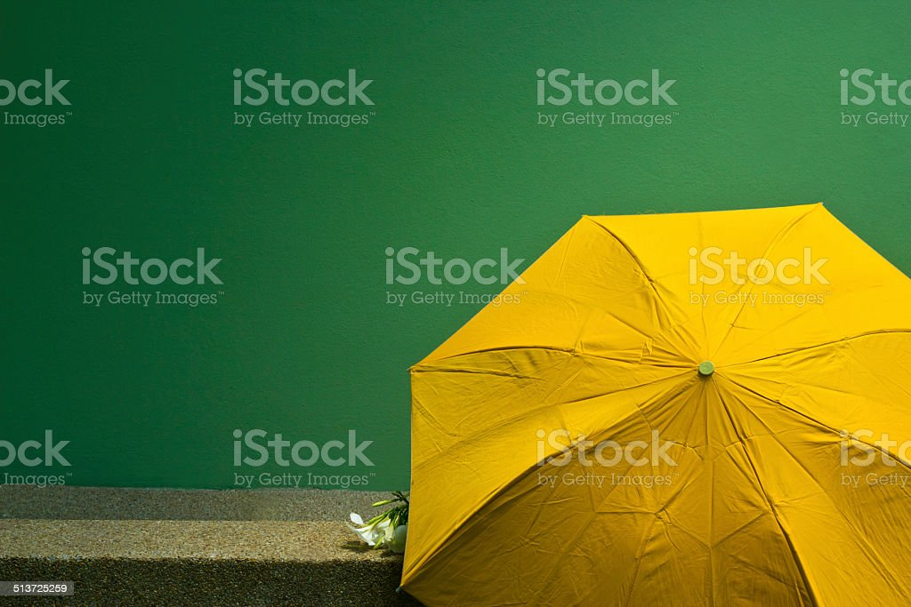 Old yellow umbrella on the green cement wall background. Concept stock photo