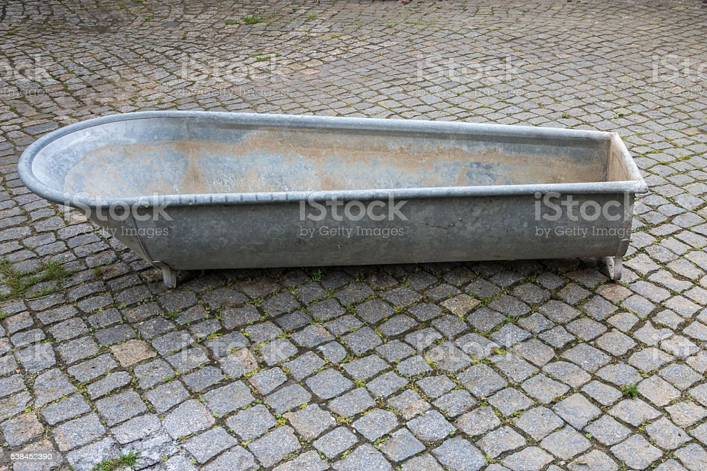 old zinc bathtub in paved courtyard stock photo