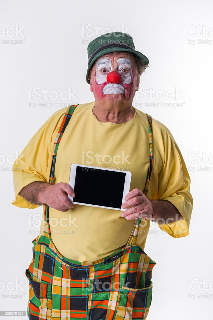 Old-aged Clown with idigital tablet stock photo
