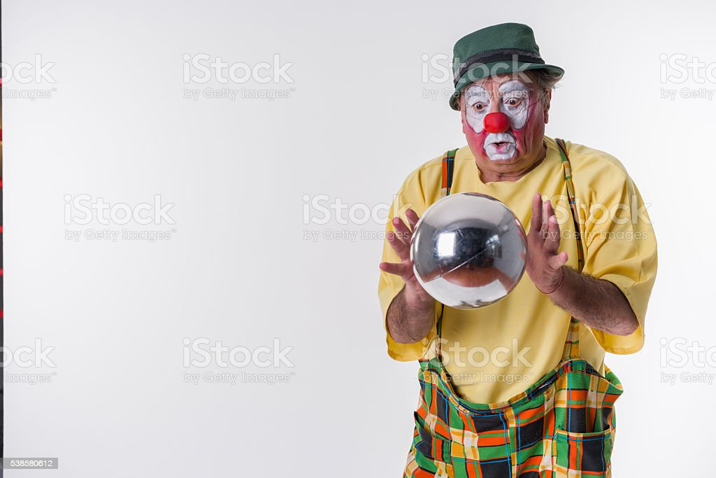 Old-aged Clown with metal ball stock photo