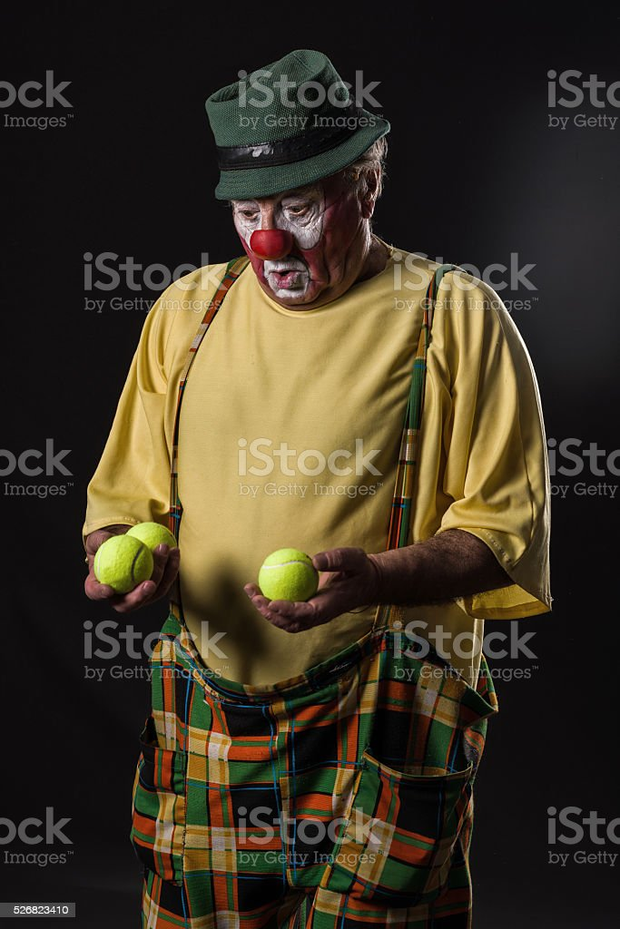 old-aged clown  with tennis balls stock photo