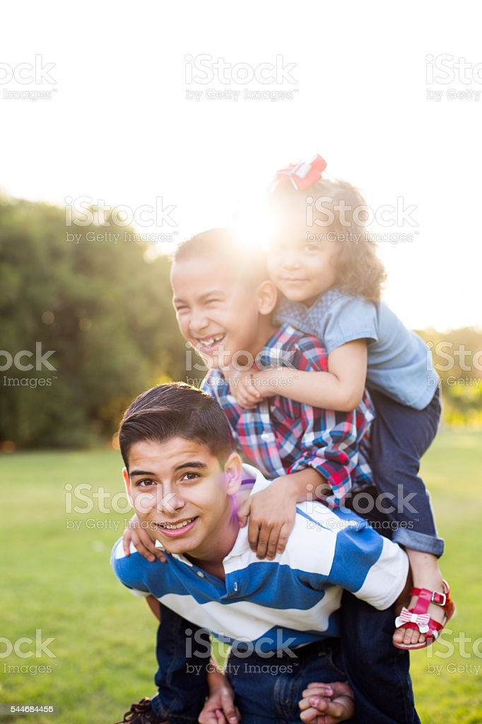Older brother carrying younger brother and sister on the back stock photo