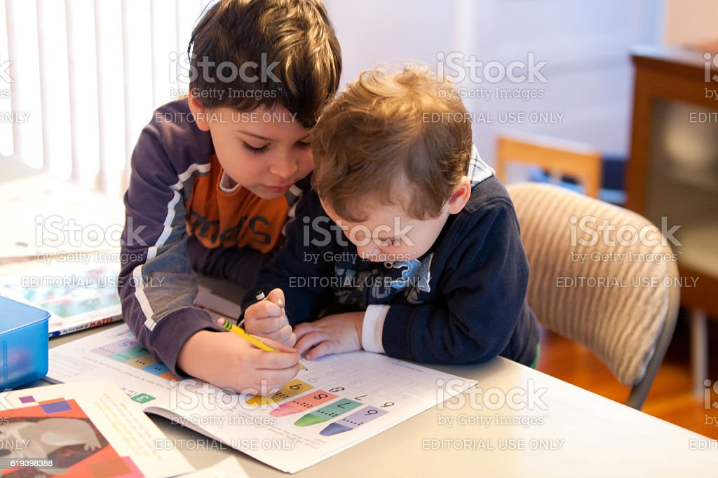 Older brother helps younger brother with schoolwork at home stock photo