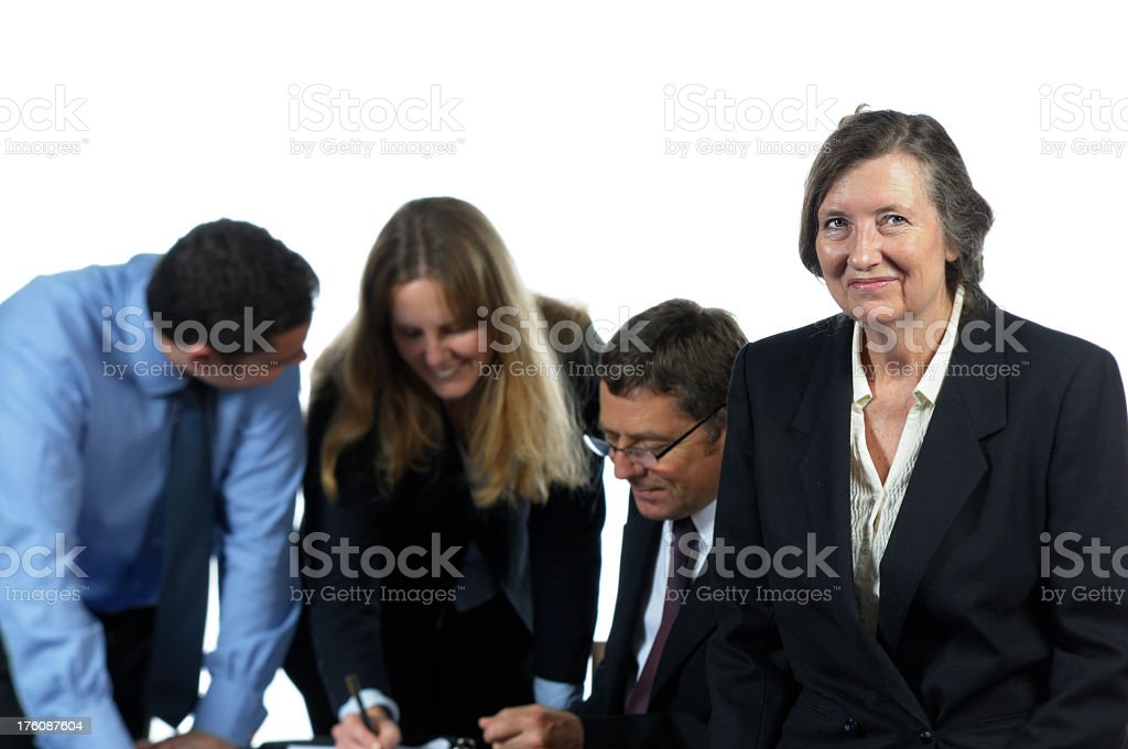 Older Business Woman and her Team Working Behind stock photo