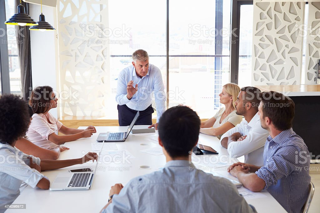 Older businessman presenting at a meeting with workmates stock photo