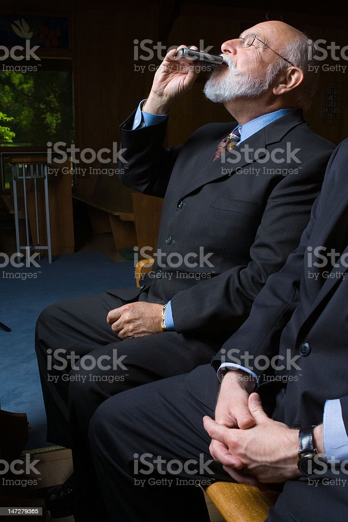 Older Caucasian Man Drinking from Flask Sitting in Church Pew royalty-free stock photo