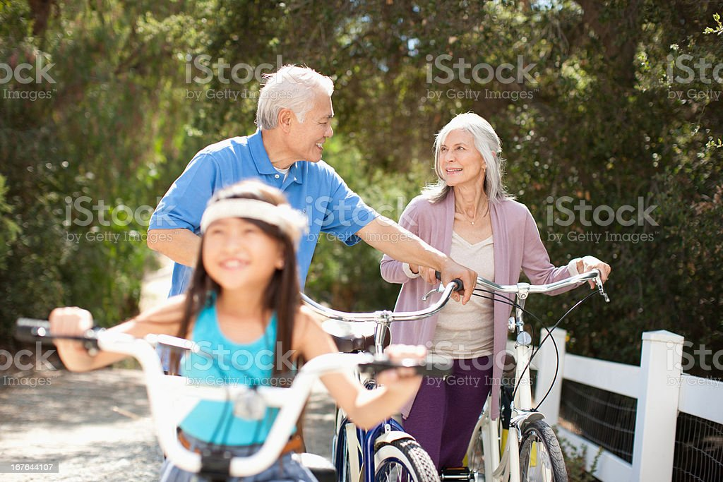 Older couple and granddaughter riding bicycles outdoors royalty-free stock photo