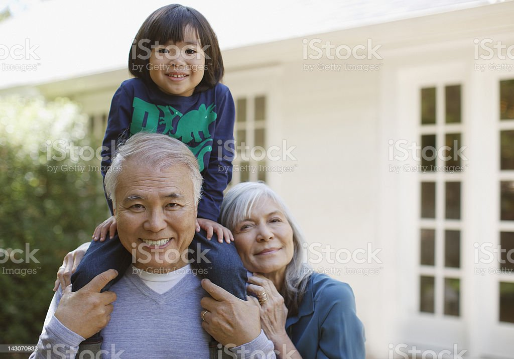 Older couple and grandson standing outdoors stock photo