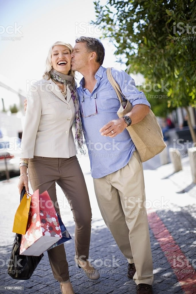 Older couple carrying shopping bags stock photo