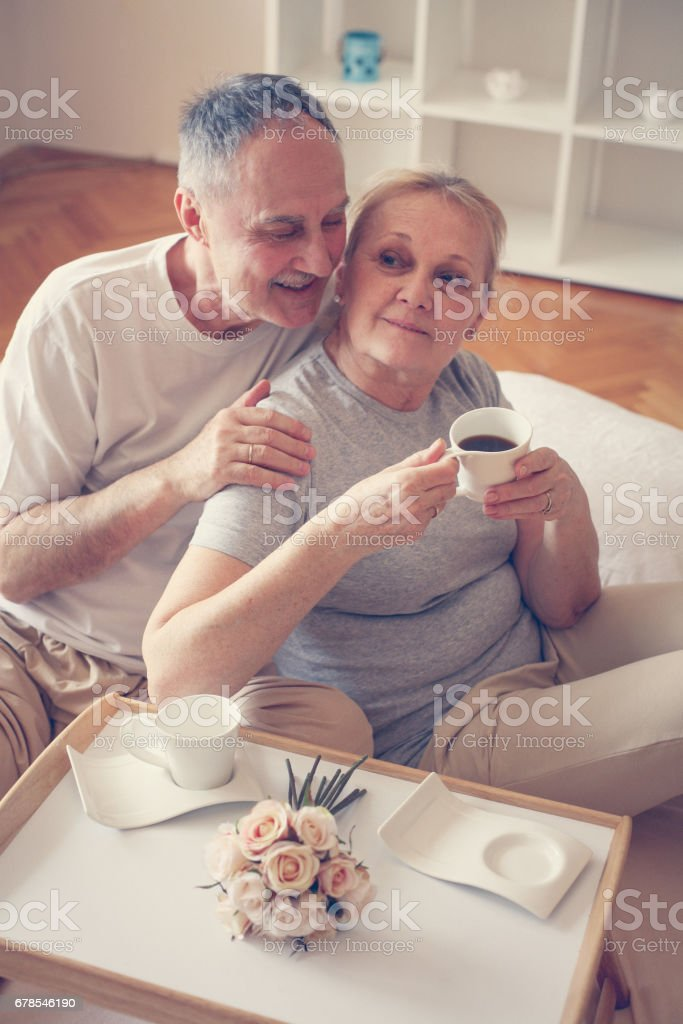 Older couple drinking coffee on bed. stock photo
