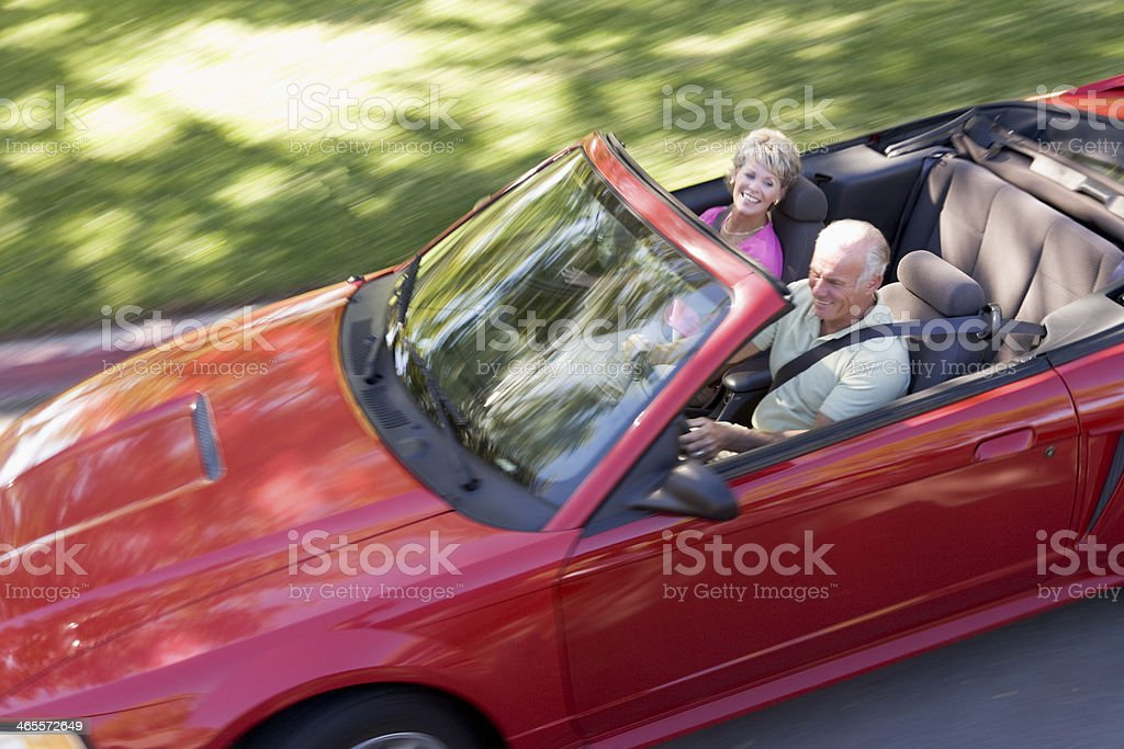 Older couple driving in convertible car stock photo