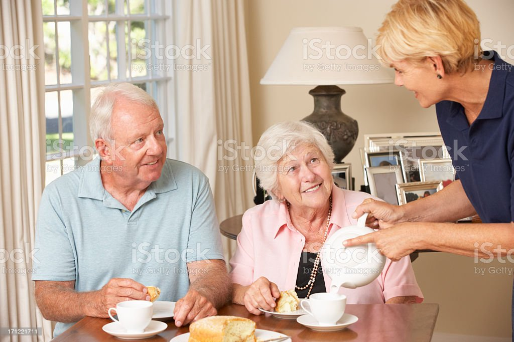Older couple having afternoon tea poured by younger woman stock photo