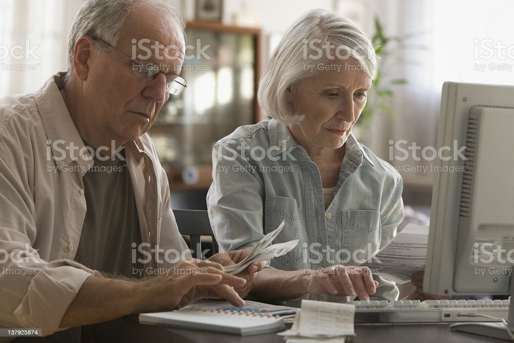 Older couple paying bills on computer stock photo
