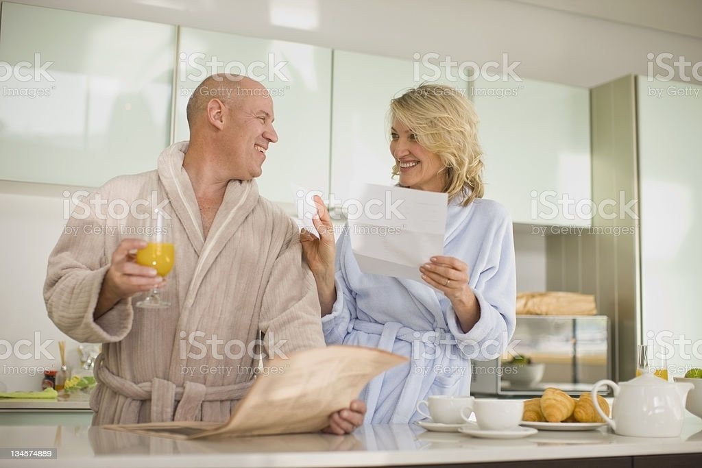 Older couple reading paper in bathrobes stock photo